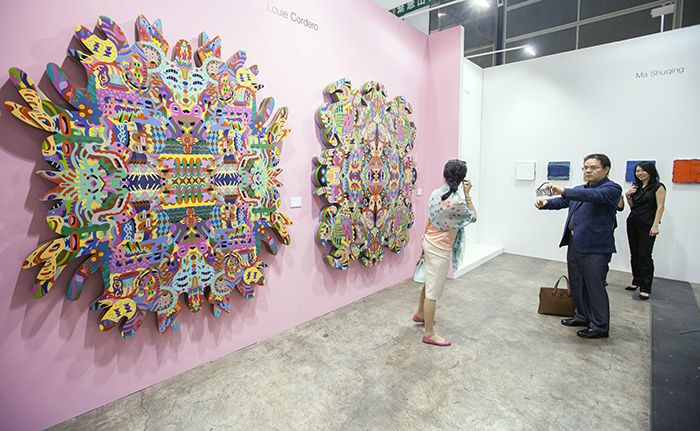 epa04205019 A man takes a photo with his phone of a woman standing in front of an artwork by Filipino artist Louie Cordero entitled 'Thinking Not Seeing, Seeing Not Thinking 1' at Art Basel 2014, Hong Kong, China, 14 May 2014. Art Basel is in its second year in Hong Kong and features 245 galleries from 39 countries. Hong Kong is the third largest art market in the world by auction revenue. The show runs from 15 to 18 May. EPA/ALEX HOFFORD