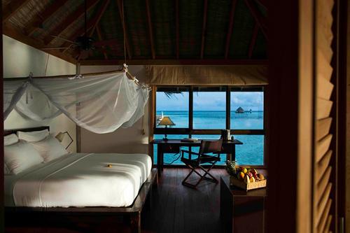 Dormitorio de una villa Gili Lankanfushi con vistas al océano.