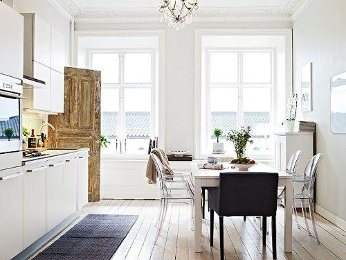 Cocina en tonos blancos con puerta de madera vieja