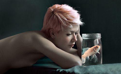 retrato de una joven contemplando un pez