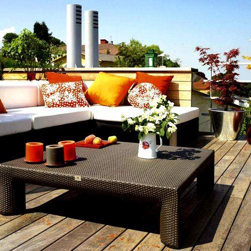 terraza con muebles oscuros y cojines naranjas