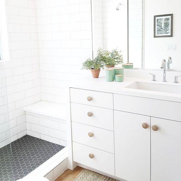 baño blanco con pomos de madera