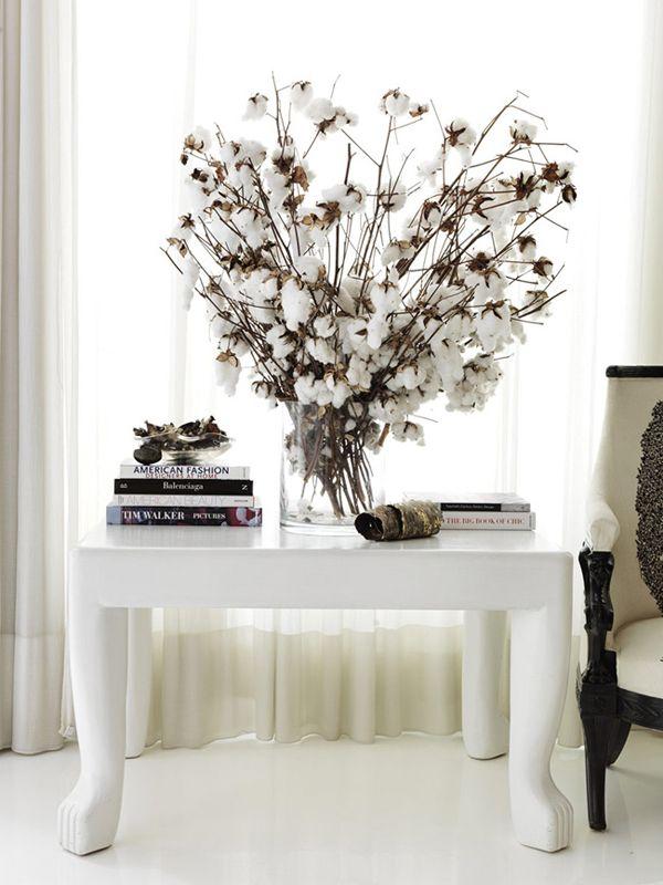 mesa blanca con libros y jarron con algodon