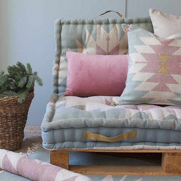 sillon pale cojines azules rosa cesto planta alfombra yute tejido