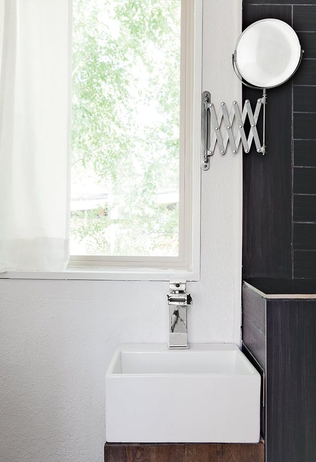 espejo plegable lateral en baño con lavabo pequeño