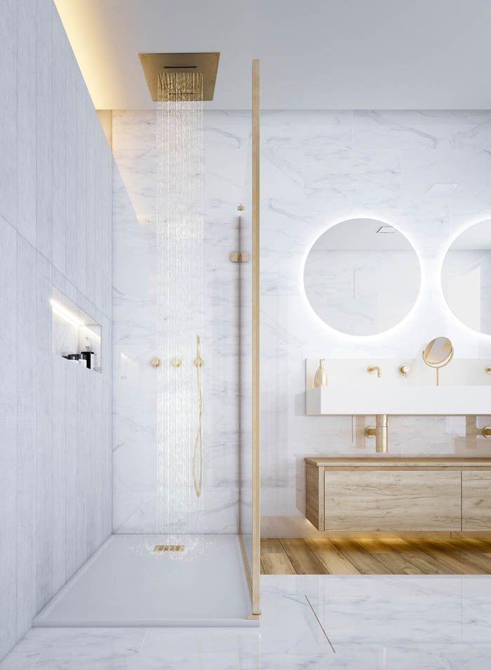 cuarto de baño dorado y marmol blanco con espejo iluminado